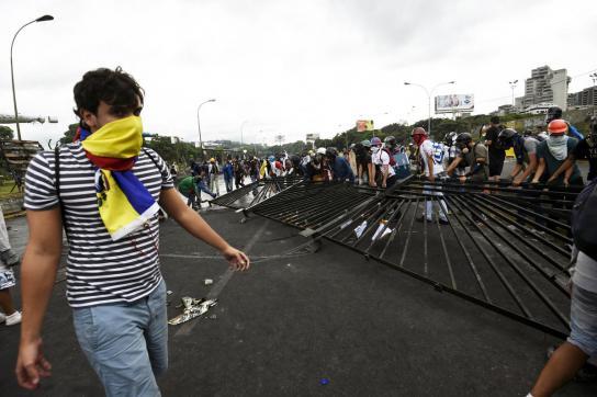 Demonstrant vor der Militärbasis Carlota in Venezuela mit ausgerissenem Gitter