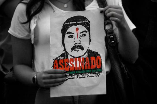 Eine Frau hält ein Poster, auf dem der ermordete Camilo Catrillanca zu sehen ist.
